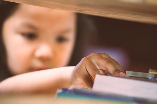 Bambina asiatica chosing un libro in biblioteca. tonalità di colore vintage