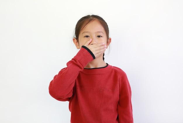 Bambina asiatica che copre la bocca con la mano isolata. il bambino ha un concetto segreto