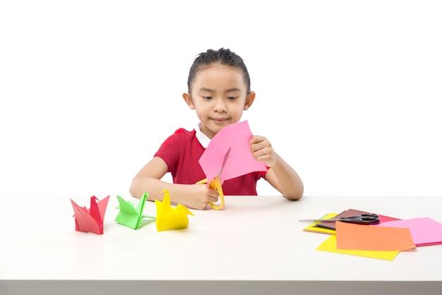 Bambina asiatica che taglia una carta isolata su sfondo bianco