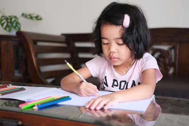 Bambina asiatica che fa attività di disegno nella sua casa