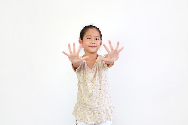 Le mani asiatiche di gesto della bambina allargano le dita su bianco
