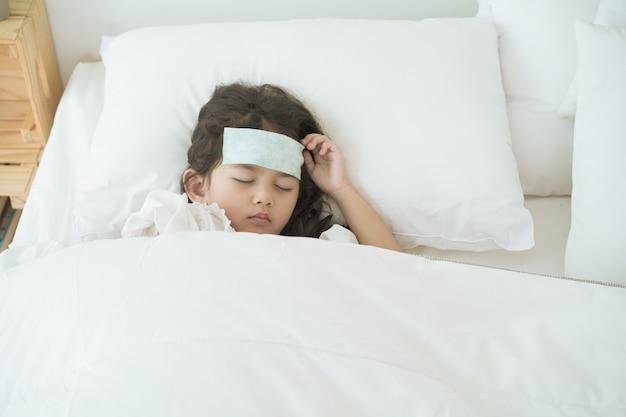 La bambina asiatica si è ammalata di virus dell'influenza e dorme sul letto, la ragazza prende un tampone per la febbre sulla fronte per mitigare la febbre.