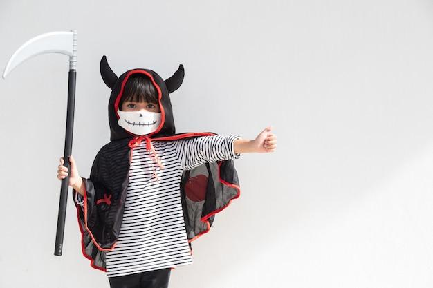 Bambina asiatica in un costume di halloween in una maschera medica. halloween con le misure di sicurezza da covid-19