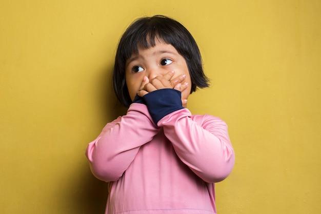 Bambina asiatica che tiene il naso a causa di un cattivo odore