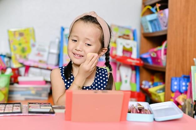 La bambina asiatica sta applicando le madri truccare e dipingere il viso con i cosmetici a casa