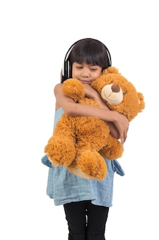La bambina asiatica sta abbracciando un orsacchiotto su un bianco