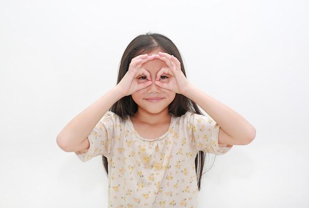 Bambina asiatica che osserva tramite il binocolo immaginario su bianco