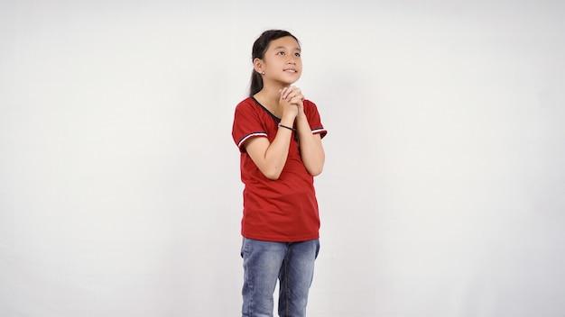 Bambina asiatica che supplica desiderio isolato sfondo bianco