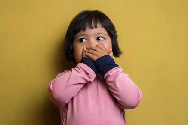 La bambina asiatica ha messo la sua mano vicino (copertura) la sua bocca