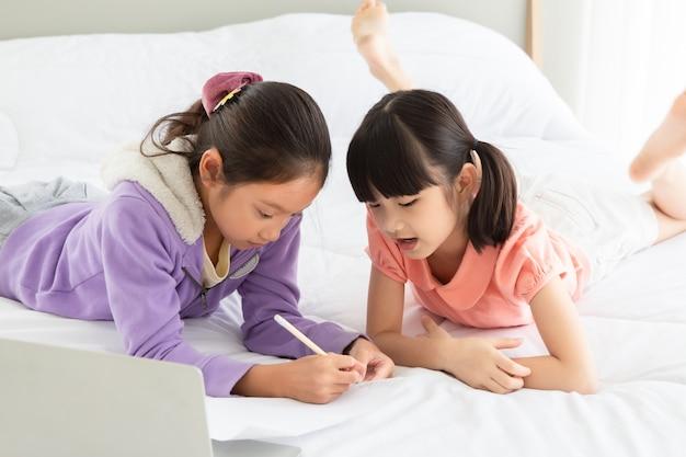 Bambina asiatica che legge il libro sul letto con il computer portatile insieme