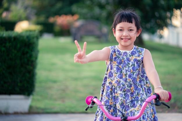 Bambina asiatica che guida la sua bicicletta fuori con il sorriso e felice