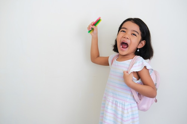 Bambina asiatica che mostra l'espressione del viso eccitata mentre indossa lo zaino e tiene in mano una penna da colorare