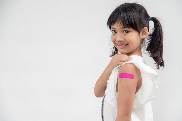 Bambina asiatica che mostra il suo braccio dopo essere stata vaccinata o inoculata, immunizzazione infantile, concetto di vaccino delta covid