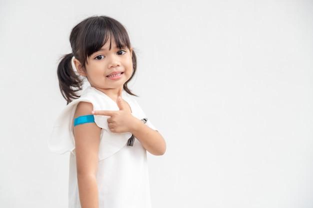 Bambina asiatica che mostra il suo braccio dopo essere stata vaccinata o vaccinata per l'immunizzazione infantile