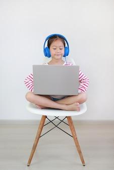 Bambina asiatica che si siede sulla sedia usando la classe di apprendimento in linea di studio della cuffia dal computer portatile