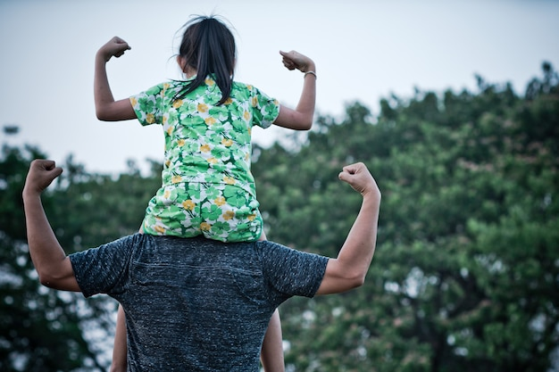 Bambina asiatica che si siede sulle spalle del padre e fa gesti forti con un sorriso e felice. concetto di festa del papà