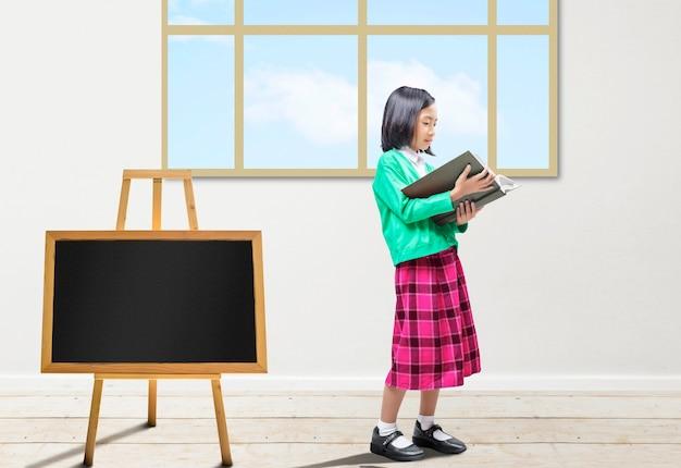 Bambina asiatica in piedi e leggendo il libro in classe. torna al concetto di scuola.