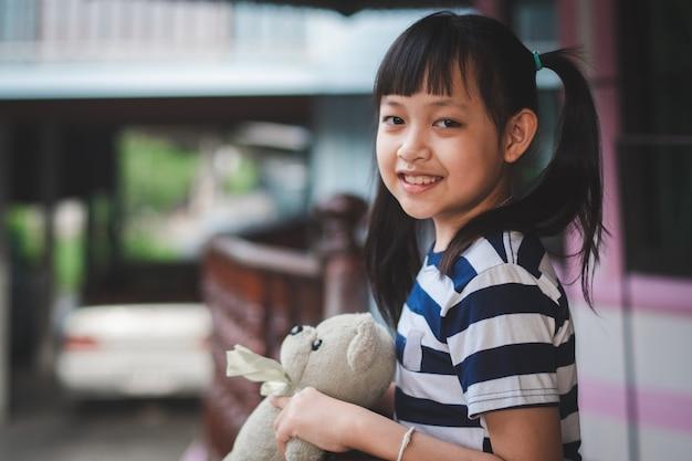 Bambina asiatica in piedi con l'orsacchiotto a casa