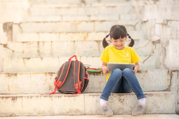 Bambina asiatica che prende lezione in linea e felice