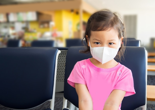 Bambina asiatica che indossa la maschera per la malattia protettiva seduto sulla sala d'attesa in aeroporto pubblico