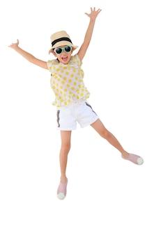 Bambina asiatica che indossa occhiali da sole e cappello di paglia che salta sul bianco