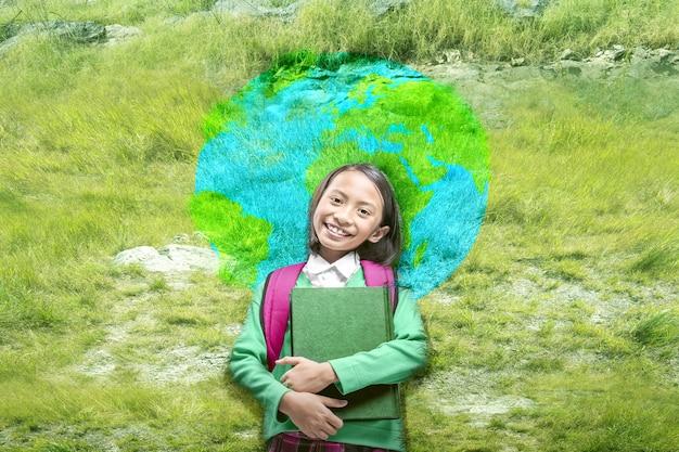 Bambina asiatica con libro e zaino in piedi con il motivo della terra