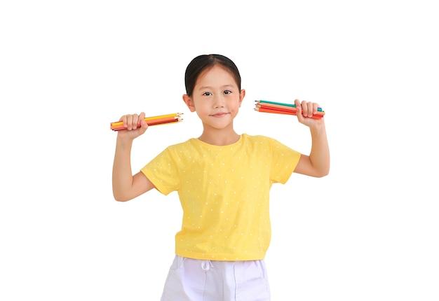 Ragazza asiatica del ragazzino che tiene le matite di colore isolate