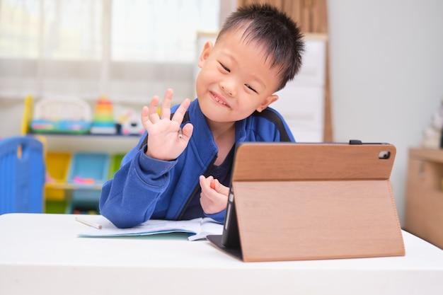 Bambino piccolo scolaro asiatico che utilizza computer portatile che studia i compiti durante la sua lezione online a casa
