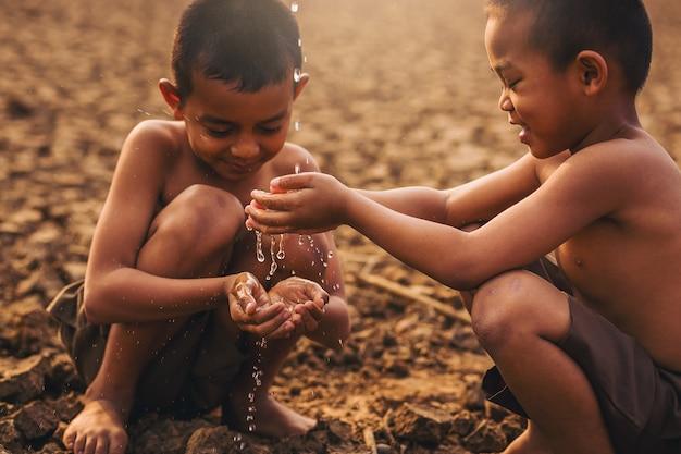 Ragazzi locali asiatici in possesso di acqua con la mano a terra screpolata asciutta cambiamento climatico conservazione dell'ambiente e fermare il concetto di riscaldamento globale