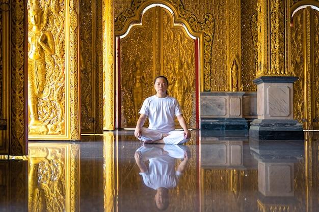 L'uomo asiatico con i capelli lunghi rilassa la meditazione con tutto il costume bianco seduto davanti alla carta da parati dorata di buddist nel tempio, thailandia.