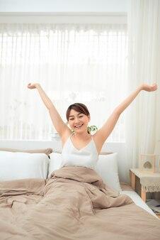 Donna asiatica dai capelli lunghi che allunga il braccio per svegliarsi la mattina