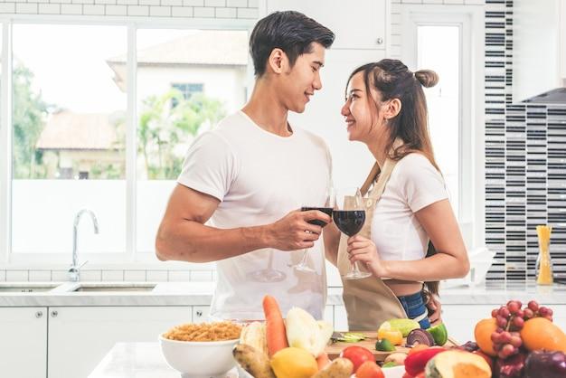 Amanti asiatici o coppie che bevono vino nella stanza della cucina a casa Foto Premium
