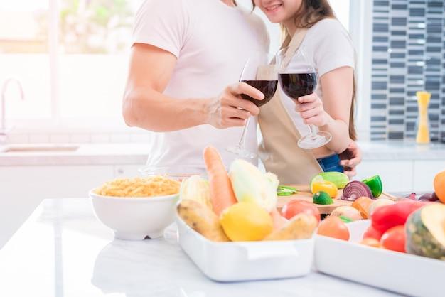 Amanti asiatici o coppie che bevono vino nella stanza della cucina a casa
