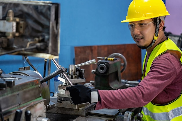 Macchinista asiatico in tuta di sicurezza che fa funzionare i torni professionali nella fabbrica di lavorazione dei metalli