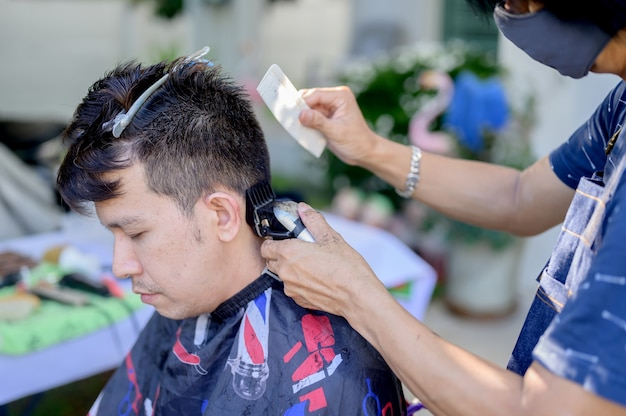 Asian facendo taglio di capelli nel giardino di casa. imparare i corsi di barbiere online durante il blocco per una nuova occupazione. nuova vita normale dopo la situazione pandemica dell'epidemia di covid-19.