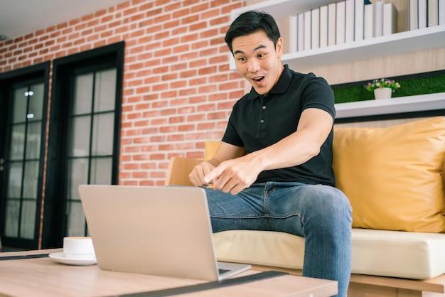Il maschio asiatico in casual si sente eccitato e indica il laptop mentre lavora.