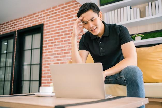 Il maschio asiatico in casual sente lo stress e si preoccupa del laptop.