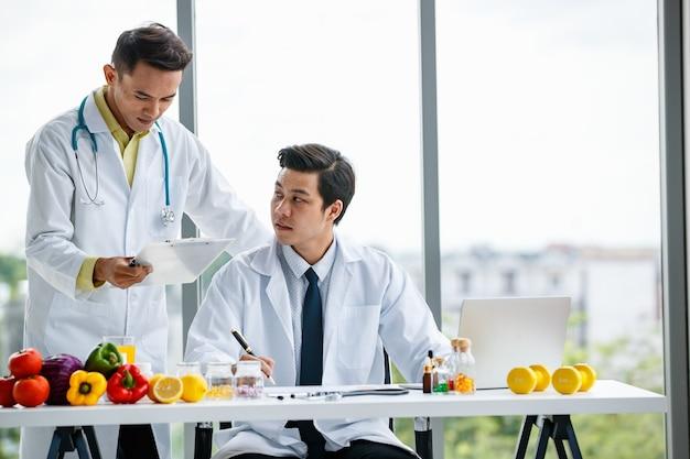 Colleghi maschi asiatici in uniforme medica che lavorano insieme sul tavolo con frutta durante il lavoro nella clinica moderna