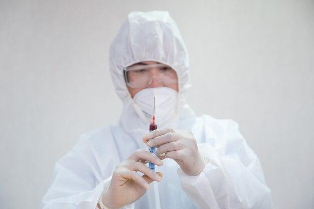 Medico maschio asiatico in siringa medica della tenuta del ppe che inietta il campione di sangue in laboratorio