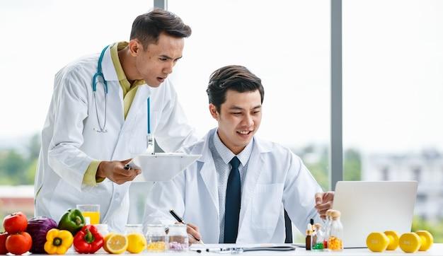 Medici maschi asiatici in uniforme che sorridono e analizzano i dati su appunti e laptop vicino a frutta e vitamine mentre lavorano insieme in clinica