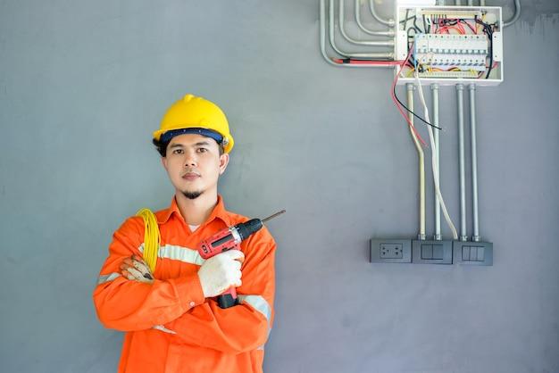 Elettricisti maschi asiatici ispezionano i sistemi elettrici negli edifici