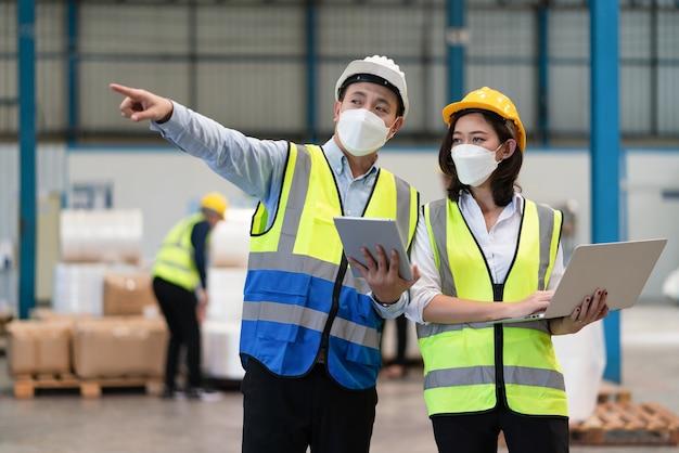 Ingegnere maschio asiatico indossa una maschera per proteggere il coronavirus con tecnico femminile che lavora in magazzino