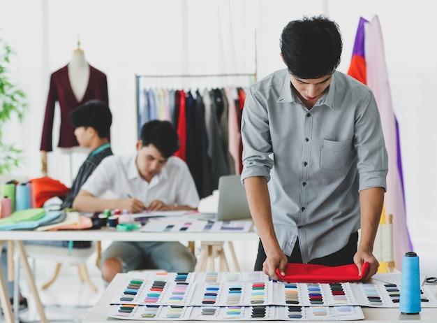 Stilista asiatico maschio che confronta il tessuto con campioni colorati mentre lavora vicino ai colleghi in atelier