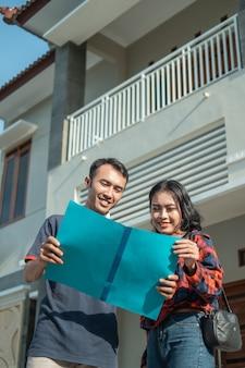 Maschio e femmina asiatici in possesso di un certificato fondiario con una nuova casa