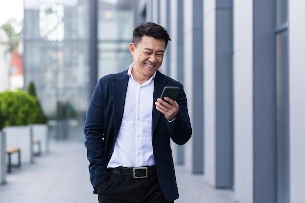 Libero professionista maschio asiatico che cammina vicino al centro affari tenendo il telefono, leggendo notizie sorridenti, uomo d'affari di successo