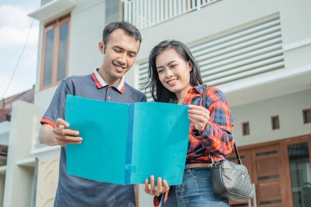 Imprenditore edile maschio asiatico che mostra i certificati di casa a belle donne contro una nuova casa
