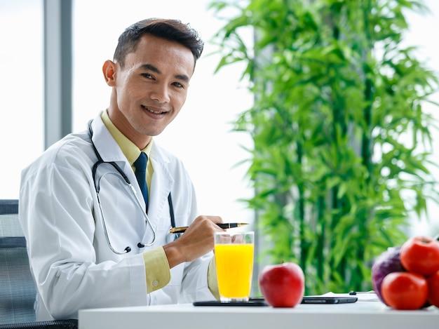 Nutrizionista maschio asiatico che stringe le mani e guarda la telecamera mentre è seduto alla scrivania con cibo sano nell'ufficio dell'ospedale moderno