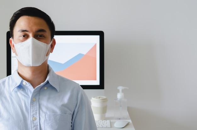 Maschera d'uso dell'ufficiale maschio asiatico per proteggere virus nella stanza dell'ufficio con la tazza di caffè e il gel dell'alcool sul tavolo di lavoro.