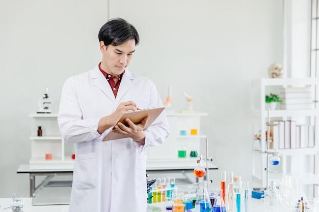 Il medico maschio asiatico dello scienziato presta attenzione che lavora in mano del laboratorio che prende nota