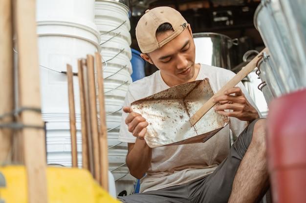 Venditore maschio asiatico che tiene un cestino della paletta quando è seduto sul pavimento nel negozio di elettrodomestici